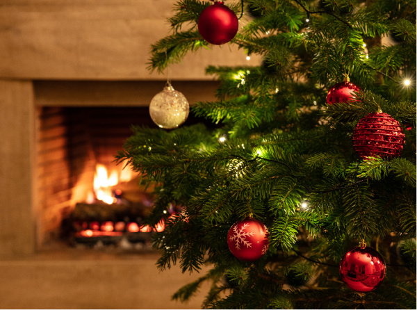 closeup of christmas tree in front of fireplace