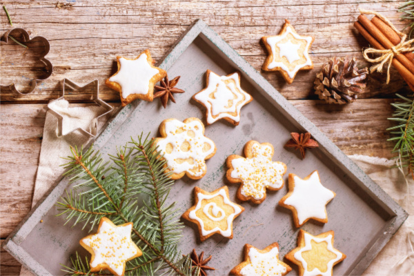 Assorted of Christmas cookies on wooden tray, served with Christmas tree branch over old table