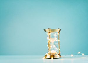 Hourglass wrapped in lights on a blue background