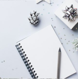 notebook on white table with christmas decor and bows