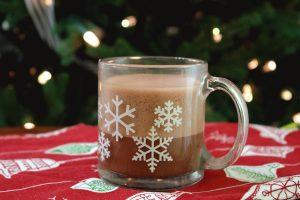 oat milk hot chocolate in snowflake mug in front of Christmas tree