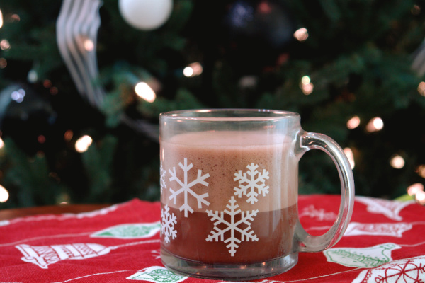 oat milk hot chocolate in snowflake mug in front of Christmas tree