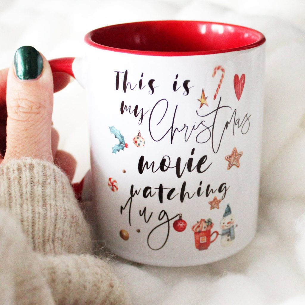"woman with green nails holding mug that says ""this is my christmas movie watching mug"" with red interior"