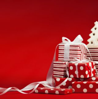 wrapped Christmas presents and ribbon in front of red background
