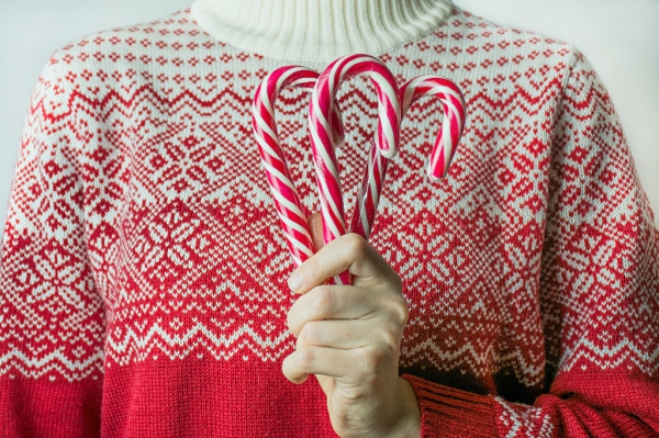 woman from neck down in christmas sweater holding candy canes