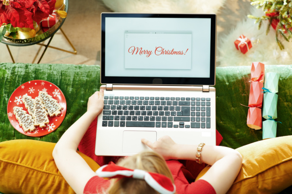 girl in red dress with merry christmas on laptop screen in front of her