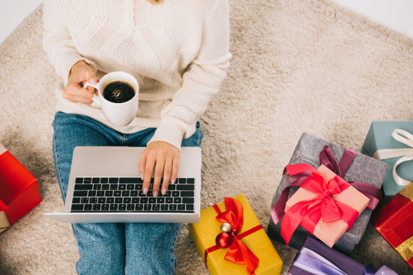 woman in white sweater and jeans with laptop in lap, holding coffee and surrounded by christmas gifts