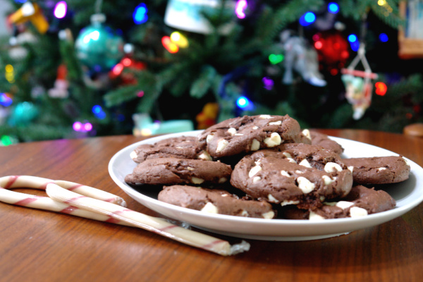 double chocolate peppermint cookies on white plate on table in front of Christmas tree