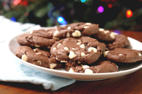 Chocolate peppermint cookies on white plate closeup with Christmas tree in background