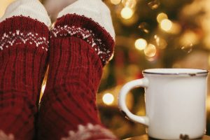 person wearing festive socks with feet on table next to white mug in front of christmas tree