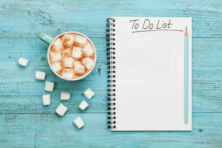 to-do list on turquoise table with hot chocolate