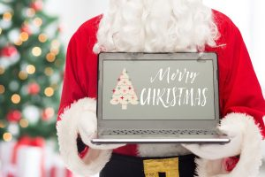 Santa holding a laptop that says Merry Christmas