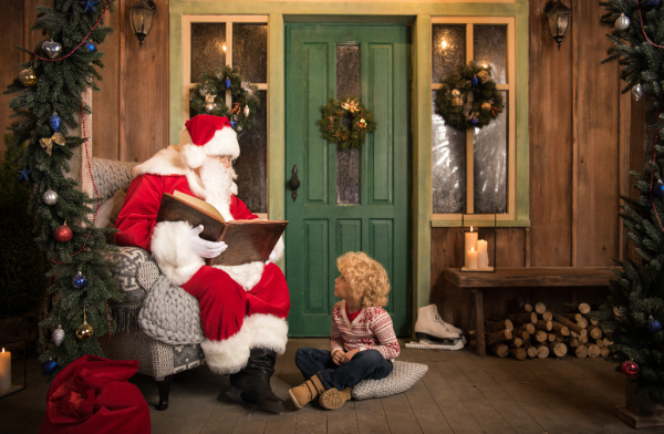 Santa reading story to kid sitting on floor