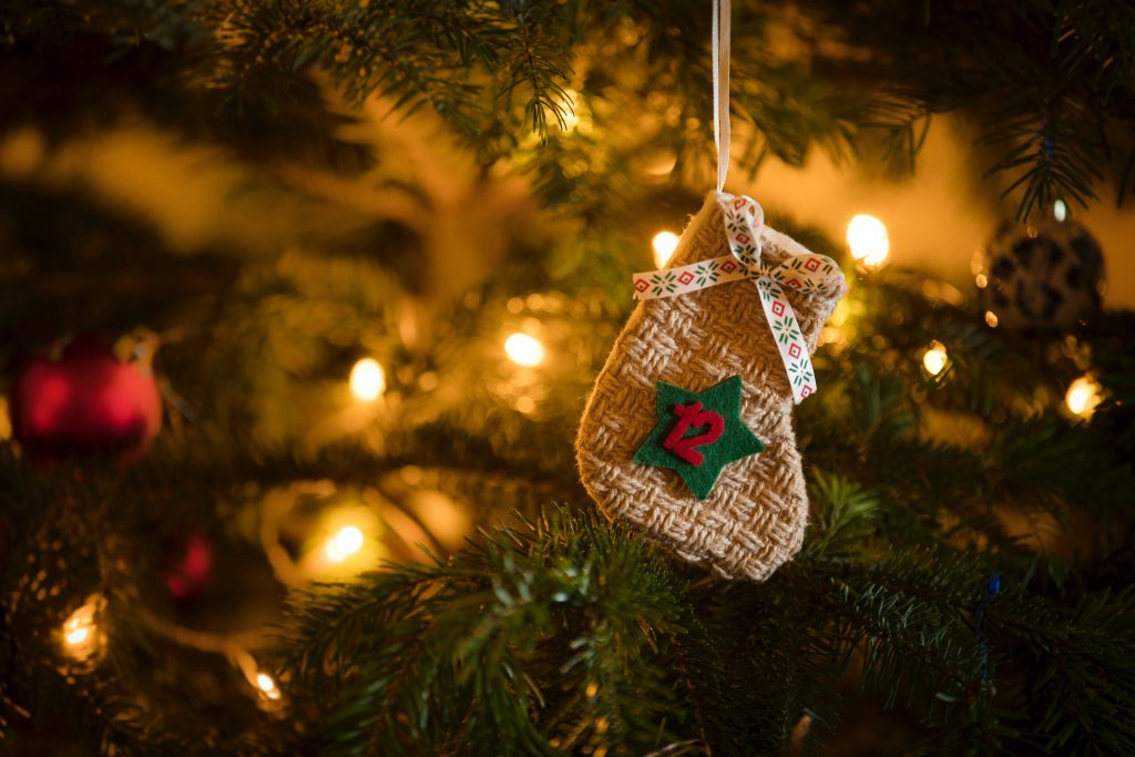 Advent Calendar Stocking with the date of the twelfth of December hanging on a traditional christmas tree.