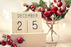 wooden calendar blocks that show December 25th with christmas decor on table