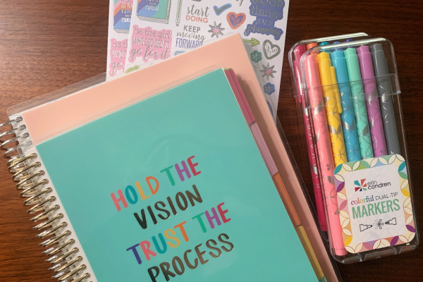 goal setting journals, stickers, and pens on table