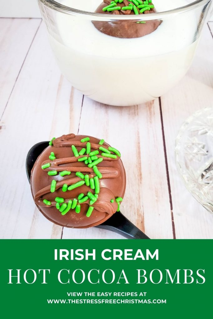 Irish cream hot chocolate bomb on spoon with one in milk glass behind it