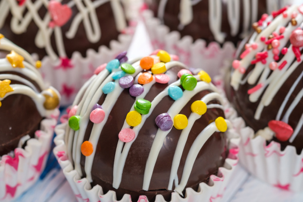 hot chocolate bombs with sprinkles and chocolate drizzle on top up close