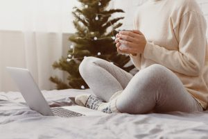 woman sitting on bed with hot drink and laptop, christmas tree in background