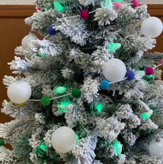 flocked christmas tree with green lights, white ornaments and rainbow garland