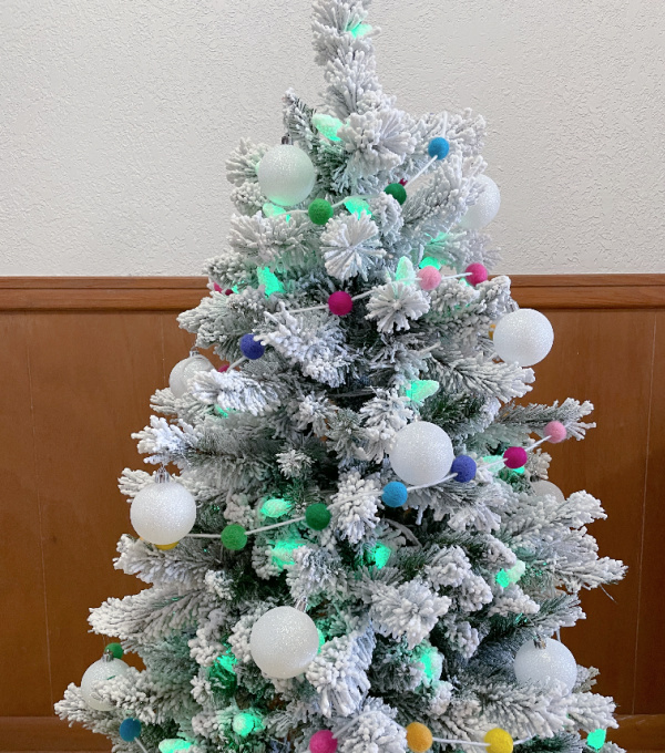 flocked st. patrick's day tree with white ornaments and rainbow ball garland
