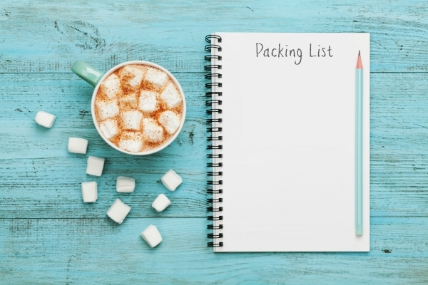 Cup of hot cocoa or chocolate with marshmallow and notebook with packing list on turquoise vintage table from above