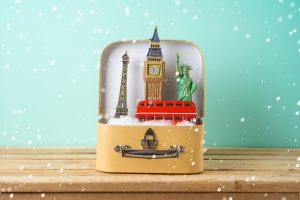 suitcase and souvenirs from around the world on wooden table