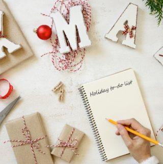 hand is writing a bucket list for winter holidays