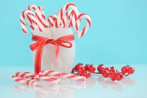 candy canes in white cup in front of blue background